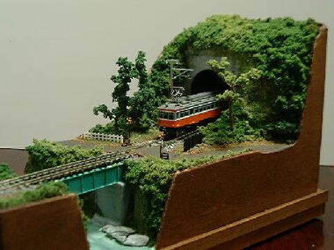 ミニらま3     小さな踏切に川とトンネルのある鉄道風景